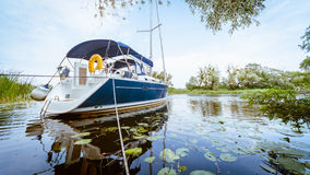 Yacht sailing on a river Stock Photo