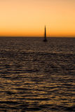 Yacht sailing in sea at sunset stock image