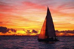 Yacht sailing at sunset. Side view of yacht sailing at sea with golden sunset and cloudscape background Royalty Free Stock Photography