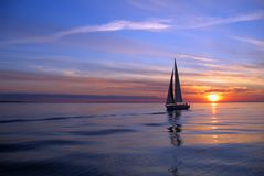 Yacht sailing at sunset. Scenic view of silhouetted yacht at sea with sunset and cloudscape background Stock Photos