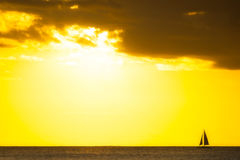 Yacht sailing at sunset along horizon Royalty Free Stock Photography
