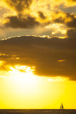 Yacht sailing at sunset along horizon Royalty Free Stock Image