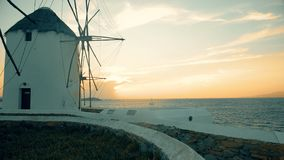 Sunset at the historic windmills on mykonos, greece. A yacht sailing at sunset behind the historic windmills on mykonos, greece stock video footage