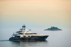 Yacht sailing at sunset Stock Image