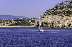 Yacht sailing towards a rocky island Stock Photos