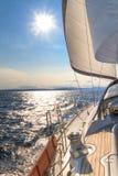 Yacht sailing towards sunset Stock Images