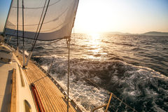 Yacht sailing towards the sunset Royalty Free Stock Photos