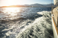 Yacht sailing towards the sunset. Luxury yachts. Royalty Free Stock Photos