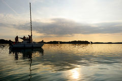 Yacht sailing towards sunset on Trakai lake Stock Photo