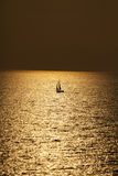 Yacht Sailing on water of ocean at sunset Stock Images