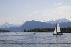 A yacht is sailing on the water. Swiss town. Beautiful mountains. The beautiful sky. Blue water stock image
