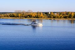 The yacht sails along the river along the autumn forest stock images