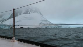 The yacht sails around the rocky coast of Antarctica. Andreev. stock video footage