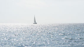 Yacht with sails in calm blue water of sea. Sailboat on horizon in the beautiful landscape. Sailing boat. Yacht sailing Stock Photo