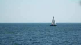 The yacht with sails floating in the sea. On the horizon are visible ships stock video