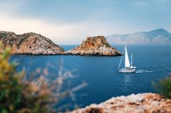 Yacht sails at Mediterranean sea between cliffs, Mallorca. Sailboat with german flag are sailing at Mediterranean sea between cliffs and rocks against the stormy Stock Image