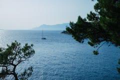 A yacht sails into the open sea in Makarska, Croatia. Royalty Free Stock Photography