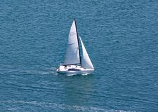 A yacht sails in the turquoise sea that surrounds Mount Maunganui in North Island, New Zealand stock image