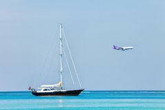 Yacht in sea and airplane on blue sky Royalty Free Stock Photos