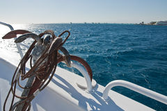 Yacht on the sea and an anchor. White yacht on the red sea and an old anchor Stock Images