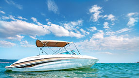 Yacht in the sea around the island. On a background of the sky with clouds Stock Photo