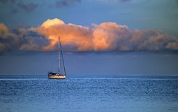 Yacht, sea and cloud. The yacht in the blue sea with red clouds in the morning Royalty Free Stock Photo