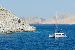 Yacht on the sea near mountain Stock Images