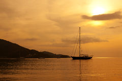Yacht in the sea at sunset Stock Image