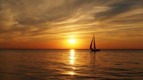 Yacht and orange sunset on sea Stock Photography