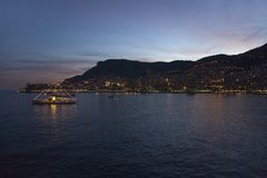 Yacht and seaside night view of Monte-Carlo with lights at dusk, in the Principality of Monaco, Western Europe on the Mediterranea Royalty Free Stock Photo
