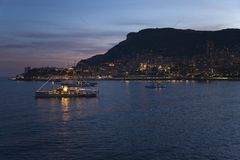 Yacht and seaside night view of Monte-Carlo with lights at dusk, in the Principality of Monaco, Western Europe on the Mediterranea Stock Photos