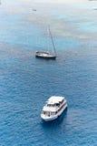 Yacht Segeln in der hohen See nahe bei einem kleinen Boot Lizenzfreie Stockfotos