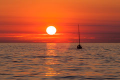 Yacht-Segeln gegen Sonnenuntergang Lizenzfreie Stockfotos