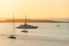 Yacht and ships at Porto Rotondo on Costa Smeralda Sardinia. Sunrise with yacht and ships at Porto Rotondo on Costa Smeralda at Mediterranean sea, Sardinia stock images