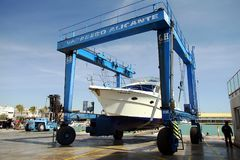 Yacht on shipyard travelift prepared for maintenance. Boat in a shipyard of Alicante city after cleaning the hull and ready for made reparations Royalty Free Stock Photos