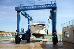 Yacht on shipyard travelift prepared for maintenance. Boat in a shipyard of Alicante city after cleaning the hull and ready for made reparations Royalty Free Stock Photography