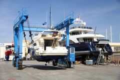 Yacht on shipyard travelift prepared for maintenance. Boat in a shipyard of Alicante city after cleaning the hull and ready for made reparations Royalty Free Stock Image