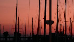 Yacht silhouette on background evening sunset at sea. Yacht harbor and boat mast. Yacht silhouette on background evening sunset at sea. Sea yachts on evening stock video footage
