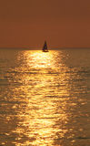 Yacht silhouetted against a golden sea. A distant yacht  silhouetted in the golden reflection of the setting sun on a rippling sea Royalty Free Stock Images