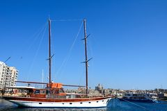 Yacht in Sliema harbour. Yacht moored along the quayside with views across the Grand Harbour towards Valletta, Sliema, Malta, Europe Stock Image