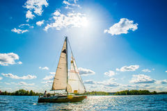 Yacht. Small yacht in blue water, sunny cloudy sky Royalty Free Stock Image