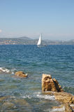 Yacht from St Tropez. Yacht in the bay with rocks in foreground from St Tropez, France stock images