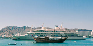 Yacht of the Sultan of Oman. The yacht of the Sultan of Oman moored in Muscat Harbor,  A traditional fishing dhow is anchored in front Royalty Free Stock Images