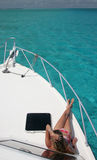 Yacht Sunbathing. Sunbathing on a bow of a yacht surrounded with turquoise ocean water. Barrier reef. Caribbean sea. Belize Stock Images