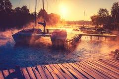 Yacht in sunrise lake. Yacht moored in sunrise lake, dawn misty time near coast Stock Image