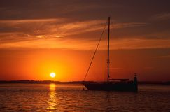 Yacht at sunset. The silhouette of a moored sailing yacht with the setting sun in the background Stock Image
