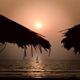Yacht in sunset on the sea. Sunset on the sea with yacht and silhouette of thatch Royalty Free Stock Images