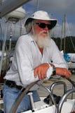 Yacht surveyor. Marine surveyor on yacht. Senior man with beard, hat and sunglasses royalty free stock images