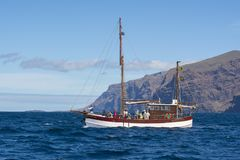 Yacht with tourists near Los Gigantes looking for whales and dolphins, Tenerife, Canary islands, Spain stock photo