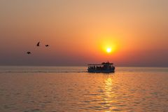 Yacht with tourists at sunset with birds flying away stock image